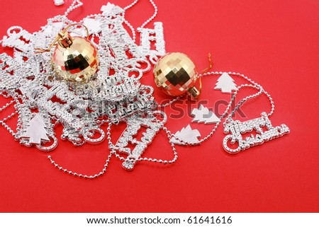 Gold Christmas ball and silver chritmas letter beads isolated on red - stock photo