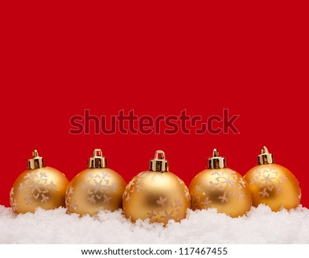 Gold christmas balls with snow isolated on red background - stock photo