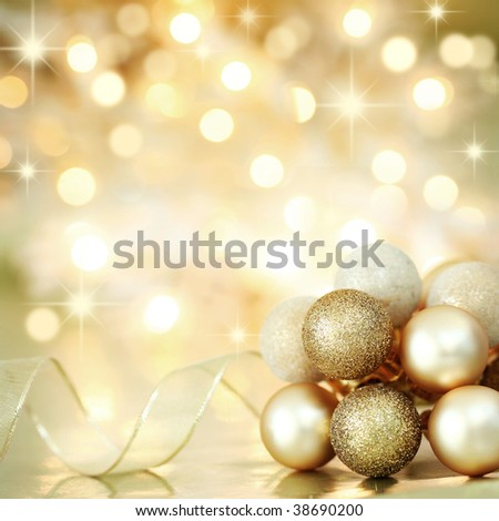 Gold Christmas baubles and ribbon on background of defocused golden lights. Shallow DOF. - stock photo