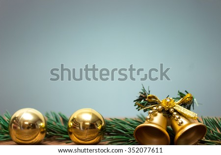 Gold Christmas bells and Christmas balls fir tree branch on a rustic wooden background. Xmas card. Happy New Year. Top view with copy space