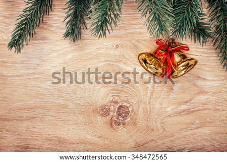 Gold Christmas bells and fir tree branch on a rustic wooden background. Xmas card. Happy New Year. Top view with copy space - stock photo