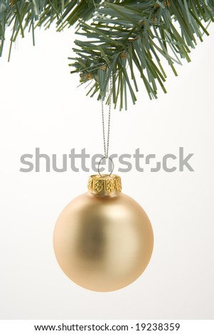 Gold Christmas Decoration Hanging From Tree Against White Background