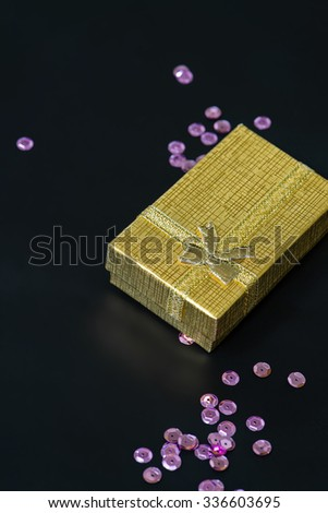 Gold christmas gift box and pink sequins on dark background - stock photo