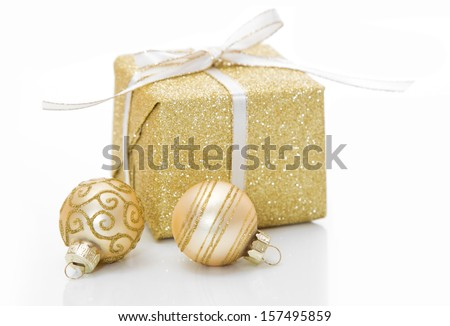 Gold Christmas gift box with bauble decorations isolated on white background  - stock photo