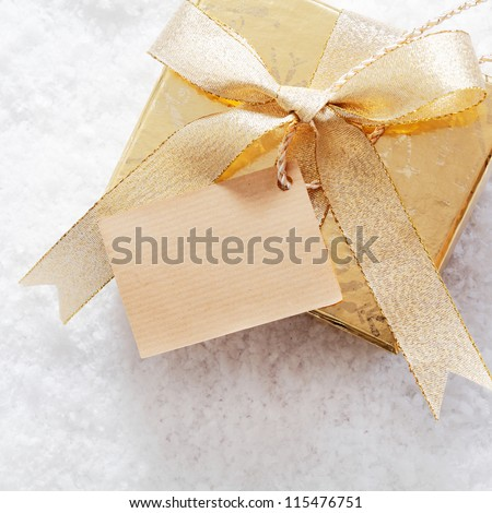 Gold Christmas gift box with blank paper label and decorative ribbon and bow standing on a bed of fresh winter snow - stock photo