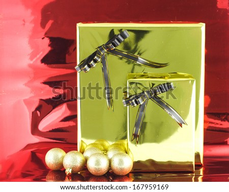 GOLD Christmas gift box with its lid propped at an angle in front to display the beautiful shiny metallic gold ribbon with falling winter snowflakes and copyspace for your greeting or wishes  - stock photo