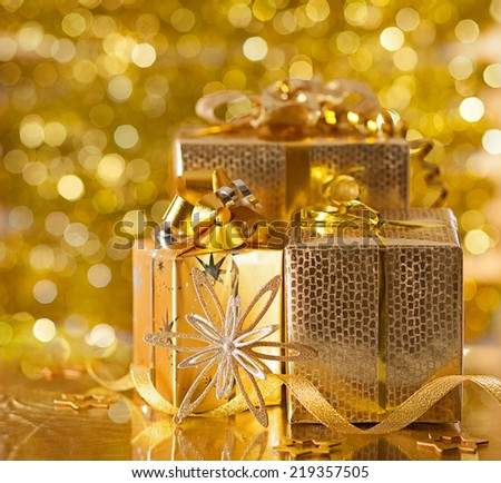 Gold Christmas gifts on background of defocused golden lights. - stock photo