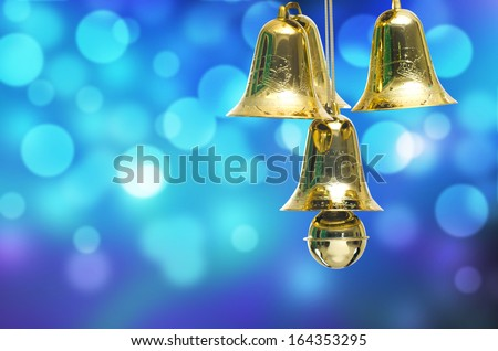 Gold christmas jingle bells on a blue bokeh background. - stock photo
