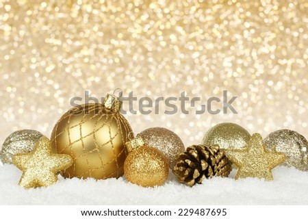 Gold Christmas ornament border in snow with twinkling gold light background