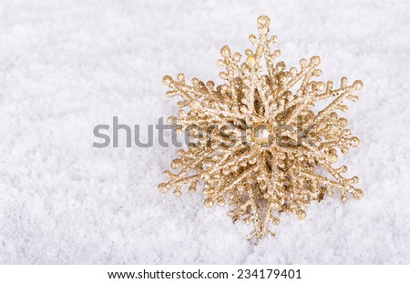 Gold Christmas ornament on a snowy white background - stock photo