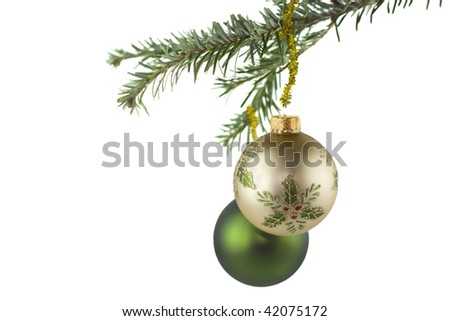 gold Christmas ornament with holly accents on fir tree - stock photo