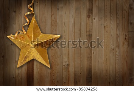 Gold Christmas star against a wooden country barn background. - stock photo