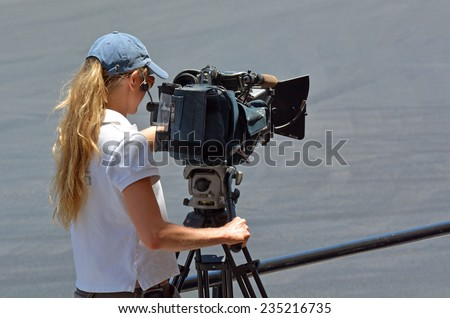 GOLD COAST, AUS - NOV 06 2014:Camerawoman filming. In 2006, there were approximately 27,000 television, video, and motion picture camera operators employed in the United States.