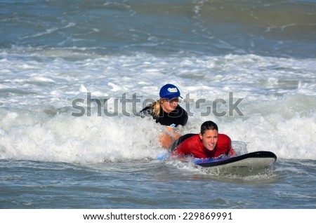 GOLD COAST, AUS - NOV 01 2014:Female wave surfing instructor teaches a woman how to surf in Surfers Paradise, Queensland, Australia. - stock photo