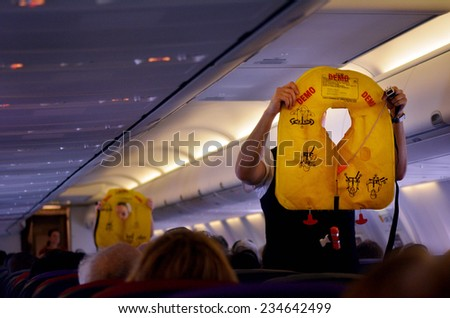 GOLD COAST, AUS - NOV 22 2014:Flight attendants during Pre-flight safety demonstration.There have been 761 deaths in 12 commercial aviation accidents in 2014, according to the Aviation Safety Network. - stock photo