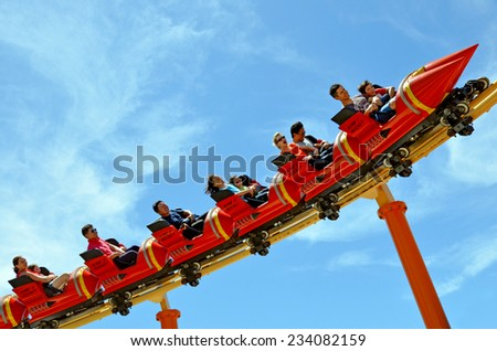 GOLD COAST, AUS -  NOV 06 2014:Visitors ride on Road Runner Roller Coaster in Movie World Gold Coast Australia.It's a 335-metre (1,099 ft) Junior Coaster reaches a top speed of 45.9 km/h (28.5 mph) - stock photo