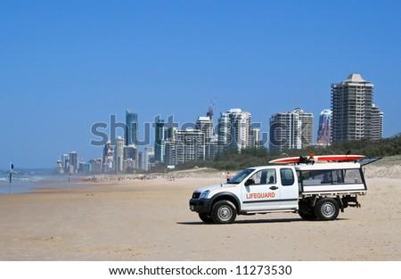 Gold coast lifeguard vehicle on the beach looking towards Surfers Paradise Gold Coast Australia. - stock photo