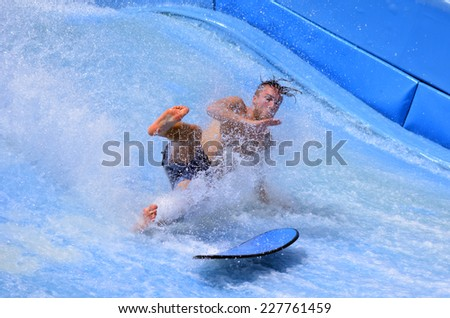 GOLD COAST OCT 29 2014: Man falling from a surfing board on FlowRider. It is a water park attraction that simulate the riding of waves in the ocean