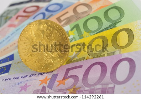 gold coin and euro banknotes - stock photo