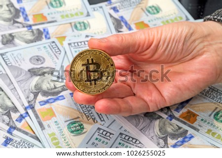 Gold coin bitcoin in hand against the background of one hundred dollar bills