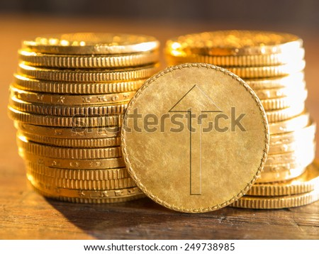 Gold coin with arrow up - stock photo