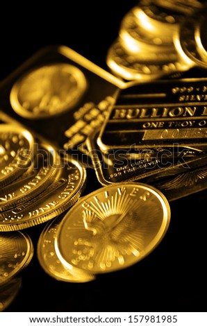 Gold coins and bullion in a pile with dark background - stock photo