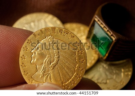Gold coins and ring with hand
