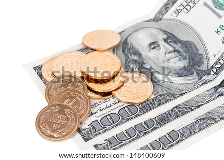 Gold coins scattered on top of one hundred dollar bills close up. - stock photo