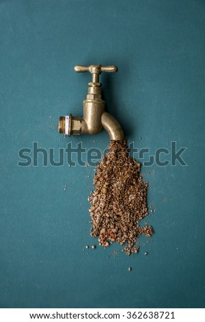 Gold color tap flowing sand and dirt. Drinking water scarcity concept shot. - stock photo