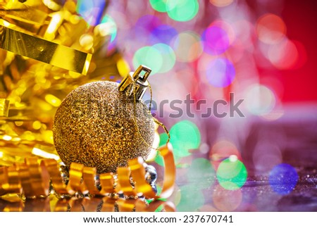 gold colored christmas ball with tinsel and tape on mirror surface and blurred background - stock photo