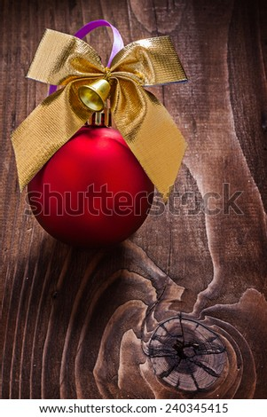 gold colored christmas bow and red bauble on old wooden board - stock photo