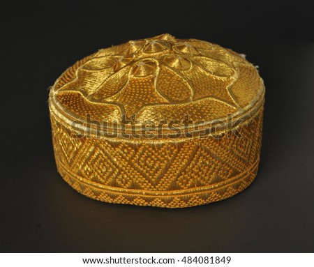 gold colored traditional asian skullcap cap on a dark background