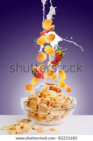 Gold corn flakes and the strawberry falls into the bowl with jets of milk on dark purple background - stock photo