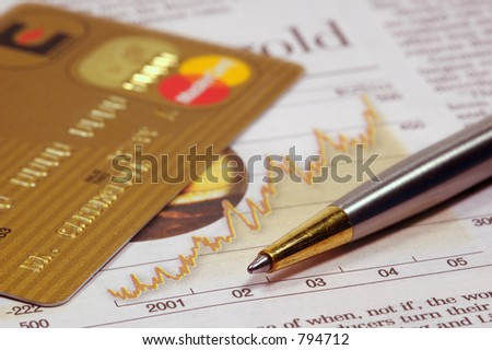 Gold credit card, financial newspaper and a pen - stock photo