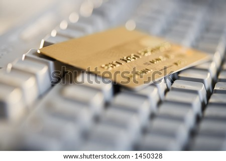 Gold credit card resting on a computer keyboard - stock photo