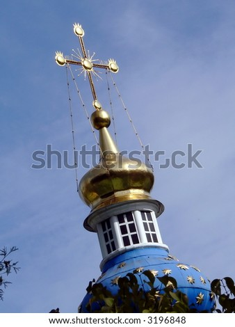 Gold cross on the sky background - stock photo