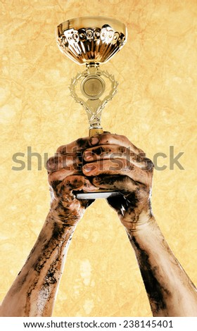 Gold cup in dirty hands - stock photo