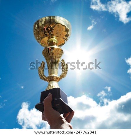 Gold cup in hands. - stock photo