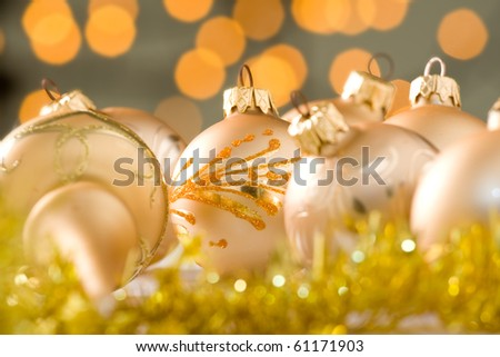 Gold decorated Christmas baubles with small lights out of focus in the background.