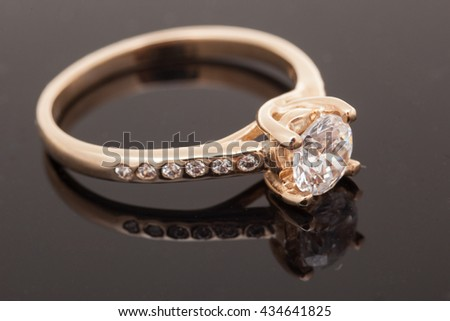 Gold diamond ring on dark background