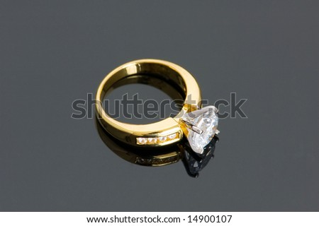 Gold diamond ring on the reflective background