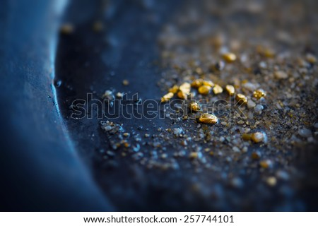 Gold dIscovery. Gold on grungy wash pan with river sand. Gold panning or digging. Very shallow depth of field due to subject size. - stock photo