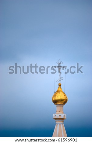 Gold dome of an orthodox temple with a cross