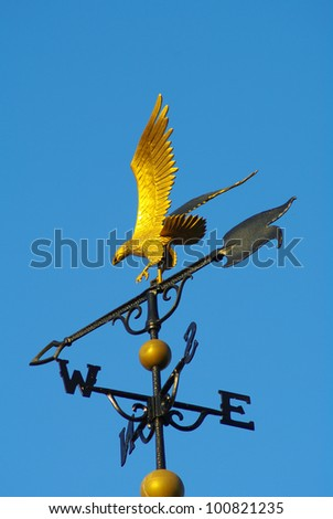Gold Eagle Weathercock on rooftop - stock photo