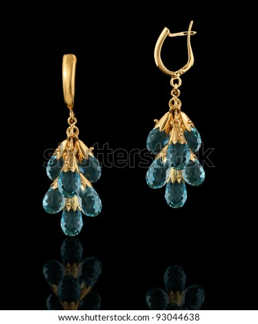 Gold earrings isolated on black background - stock photo