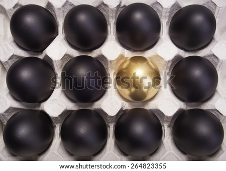 gold Easter egg between many black eggs in container - stock photo