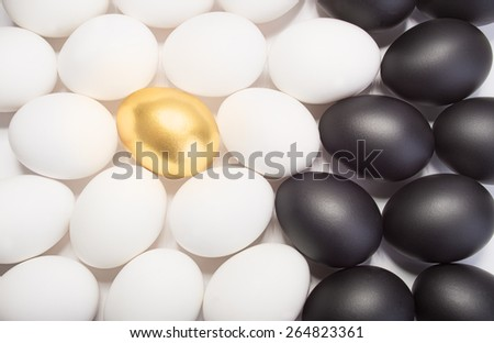 gold Easter egg between many white and black eggs on white background - stock photo