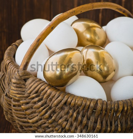 Gold egg among ordinary eggs in the basket on wooden background. Selective focus - stock photo