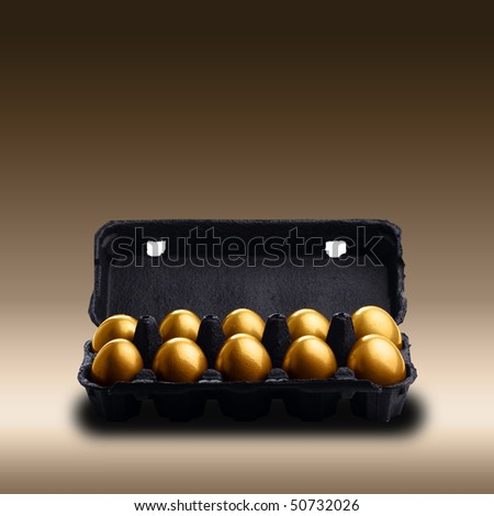 Gold eggs in a black carton on brown background - stock photo