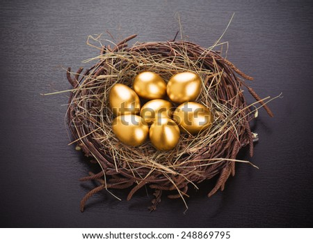 Gold eggs in nest from hay on table - stock photo